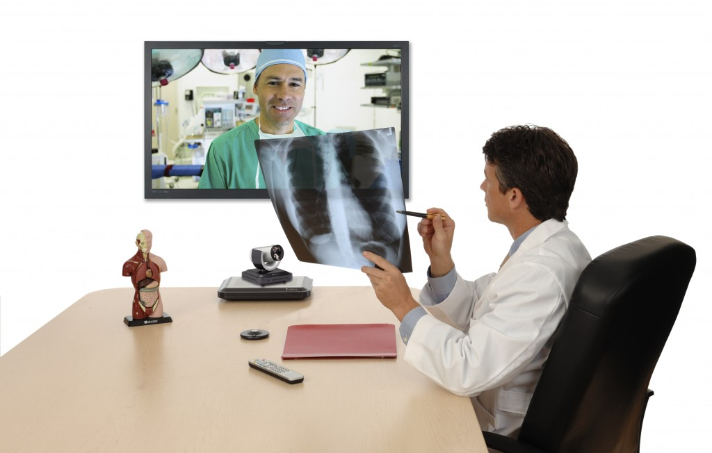 Doctor speaking with surgeon via Lifesize Video Conferencing, holding xray and showing to far end surgeon.