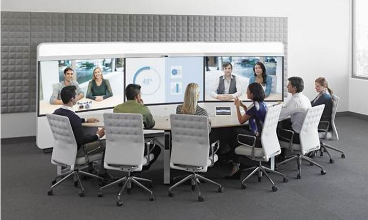 Cisco IX5000 Immersive Telepresence Suite in use. 3 screens, middle with data, 6 grey chairs close side of oval table.