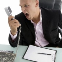 Man shouting at desk phone