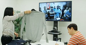 SRG holding textiles up to Polycom Video Conferencing System