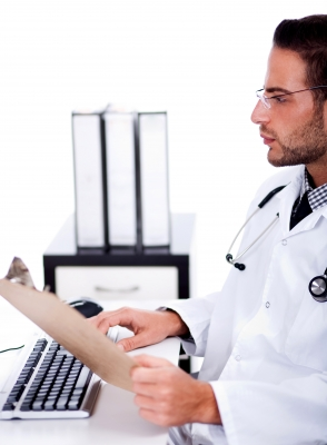 Consultant working at PC with files in hand