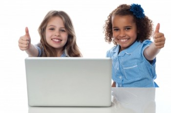Children using Video Conferencing in Classroom on laptop with thumbs up