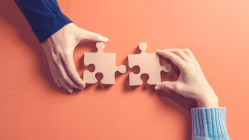 Two hands holding jigsaw, Concept for teamwork Building a success.